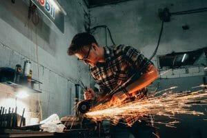 En man som jobbar med en vinkelslip